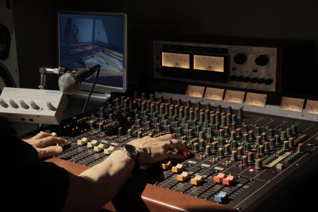 A music producer would find the recording, mixing and sometimes the mastering engineers for a record.