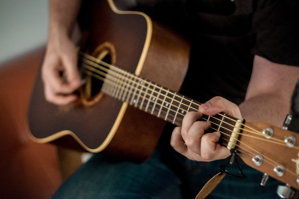 If a guitar is played on your right side, the right ear will hear the full frequency spectrum, whereas the left will hear the source with a slightly truncated high-frequency range.